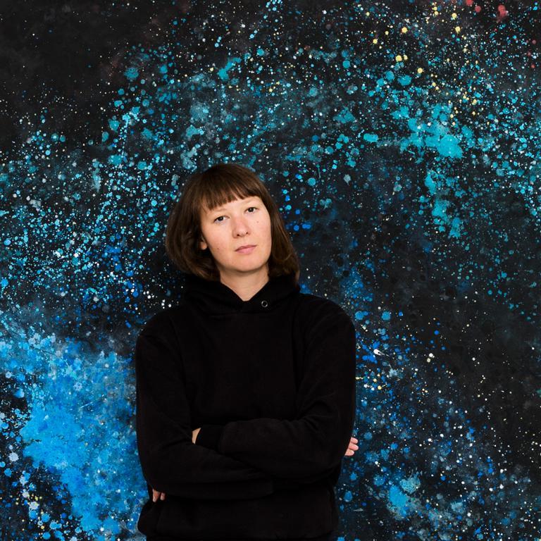 Portrait der Berliner Fotografin Caroline Wimmer aufgenommen vor einem selbst gemalten Foto Backdrop im Studio ATP24 am Treptower Park